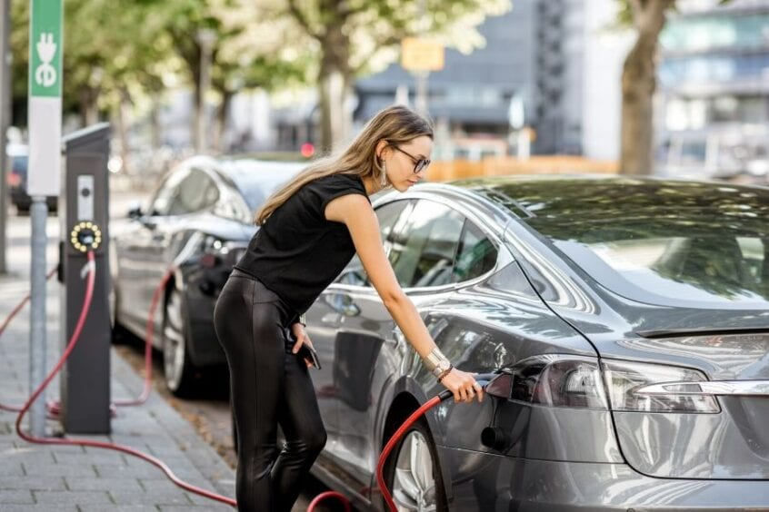 women is charging her electric car on the street parking