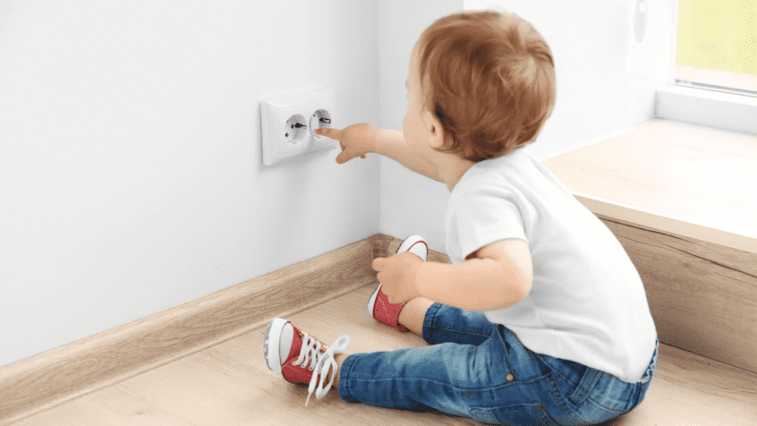 visual image of child putting their fingers near electrical outlet